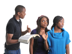 A young man trying to share the Bible with two young women.