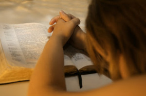 girl praying over Bible